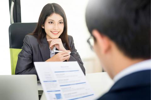 Image of an interviewer meeting with a smiling job seeker.