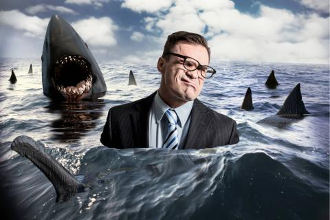 Illustration of an employee in the ocean surrounded by sharks.