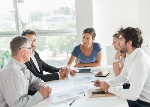 Business team sitting at a white table in conference room meeting with a consultant.