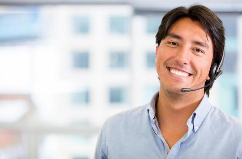 How to Become a Customer Service Specialist — Smiling man with headphone in office