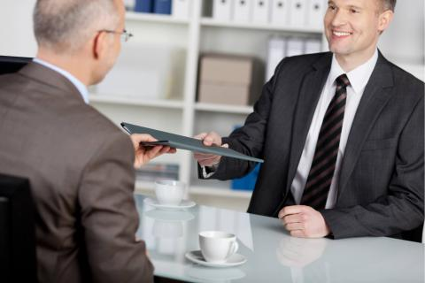 15 Questions for a Second Interview and How to Answer Them — man at table handing folder to another man