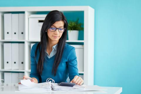 How to Advance on the Payroll Career Path — woman in office looking at notebook