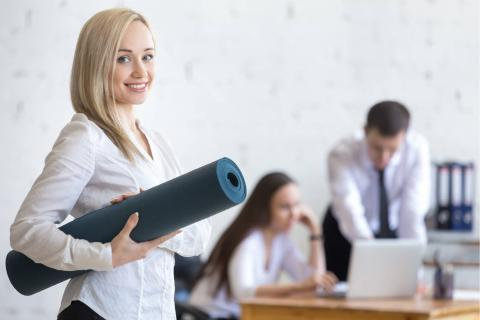 Boost Your Hiring Efforts With a Workplace Wellness Program — worker with yoga mat in office