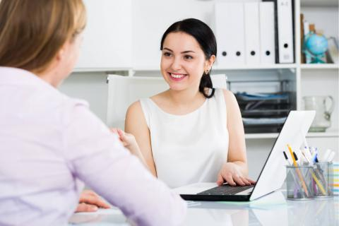 7 Ways the Contingent Workforce Can Help With Payroll — woman with laptop smiling at another women at her desk