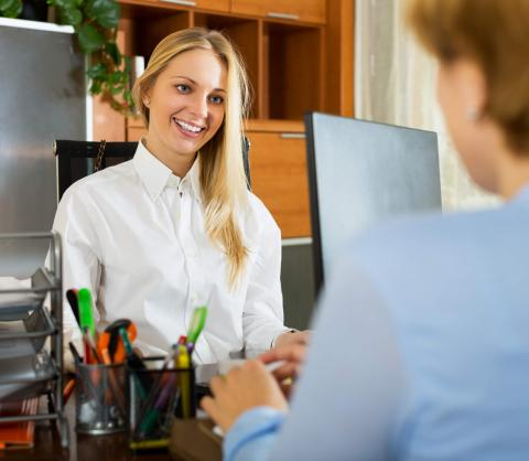 What Does a Payroll Clerk Do? Find Out If You Need One — woman smiling at another in office setting