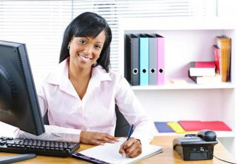Temporary Work as a Career Option? 6 Myths, 6 Realities — smiling woman working at office desk with pen, paper, computer and phone