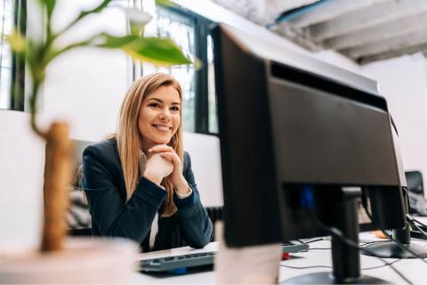 How to Be More Productive at Work — Woman smiling at computer monitor in office