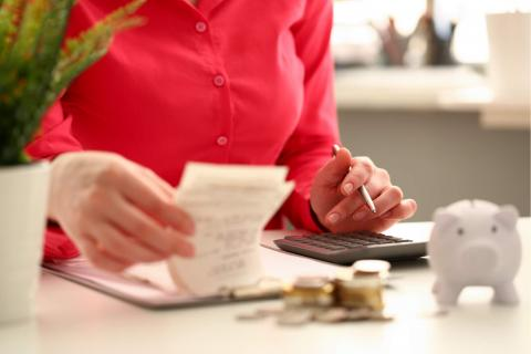 Are You Paying Your Payroll Clerks Enough — office worker with calculator, receipts, piles of coins and piggy bank