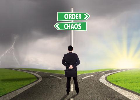 "Man with a briefcase, standing at a crossroads, in front of signs pointing in opposite directions that read: ""Order"" and ""Chaos."""