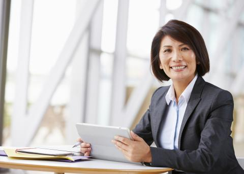 A smiling businesswoman sitting at a table in a bright office space, holding a tablet computer.