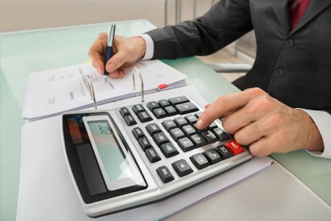 All You Need to Know About CPA Jobs — Person in suit using calculator and pen at desk
