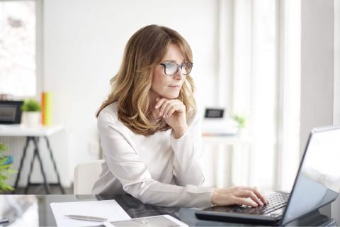 A woman wearing glasses, sitting at a desk in a home office and working on a laptop.