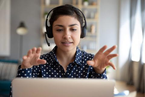 How to Make the Most of Online Events and Conferences — woman with headphones and expressive hands in front of laptop