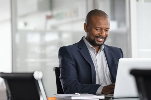 A businessman sitting at a desk, working on a laptop and smiling.