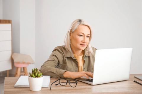 A woman with gray hair and a khaki shirt looking at a laptop in a home office.