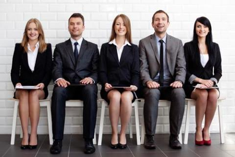 Five people sitting in a row for a job interview