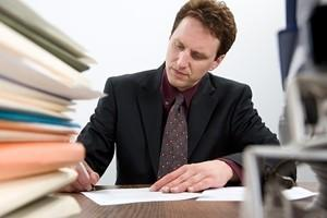 A lawyer works diligently at his desk to increase his billable hours