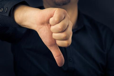 Man with a thumbs down gesture.