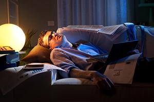 Man sleeping with his work after obviously working too hard