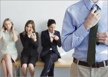 Man adjusting tie as he waits with three others for a job interview