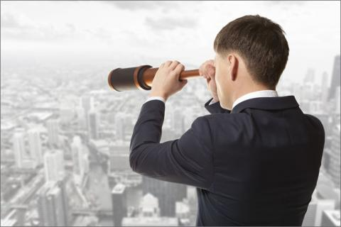 Man looking at city with telescope