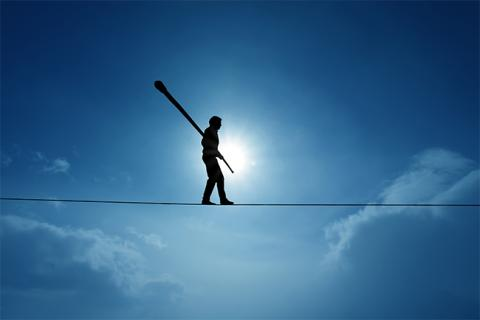 Man walking on tightrope, signifying career risks