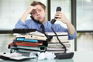 Man with stack of work, obviously not having fun at work