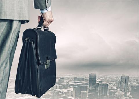 Thinking of a Job Relocation? 6 Things to Know First — man standing with briefcase, looking down at a city