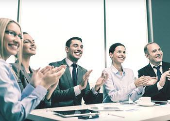 Group of people clapping, ostensibly giving workplace recognition