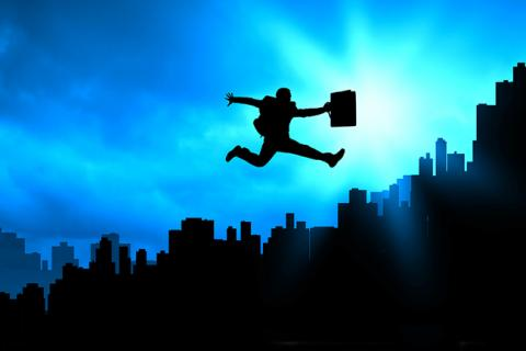Man hopping above a city with his briefcase as a symbol of changing jobs