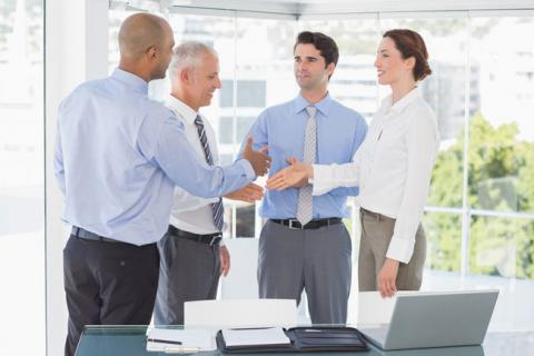 Four people shaking hands in office