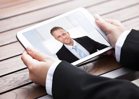 Man holding a tablet during a video interview