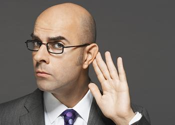 Man holding ear as if to hear what etiquette mistakes managers make