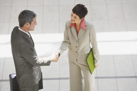 Professional man and woman shaking hands and using the elevator pitch