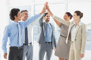 Group of accounting professionals doing a high-five after tax season