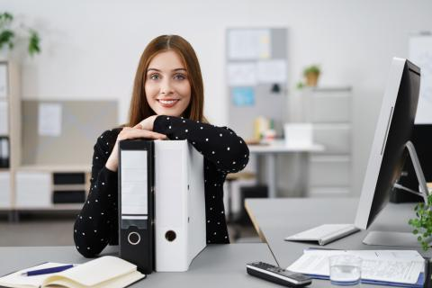 Photo of a woman at a desk with a computer and two binders.