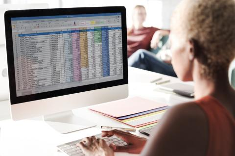 An administrative professional uses Microsoft Excel tips and tricks while on the job