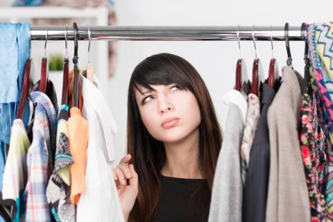 An administrative assistant searches her closet for the right office attire