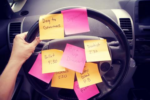 Image of a steering wheel with many post-it notes with tasks to do written on them.