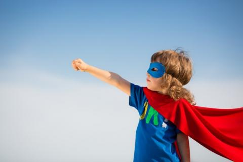 A child in a superhero outfit reached to the sky