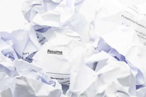Image of crumpled resume in trash.