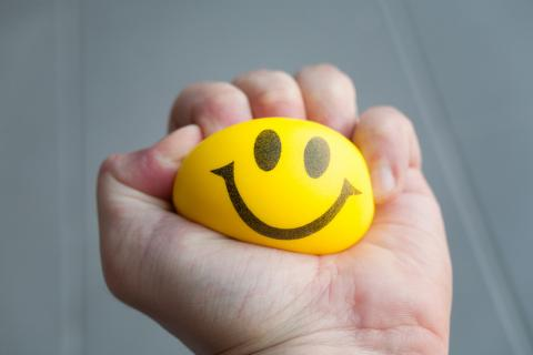 Photo of a hand squeezing a stress ball.