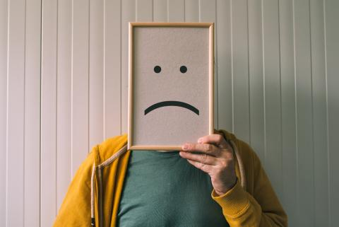 Photo of a man holding a frowning face sign.