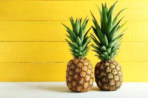 Two pineapples against a yellow background