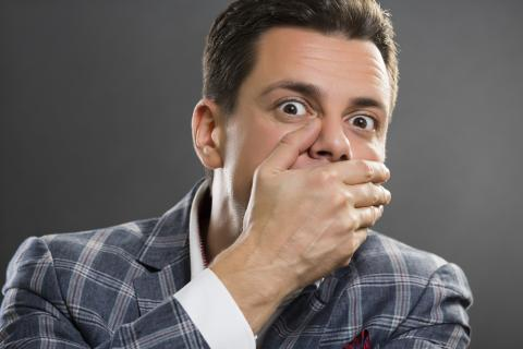 Job candidate covering his mouth with his hand.