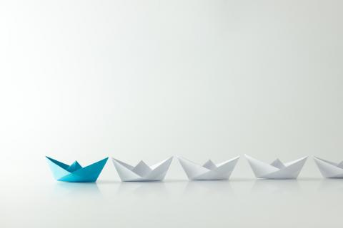 White paper ships in a line with a blue one in the lead.