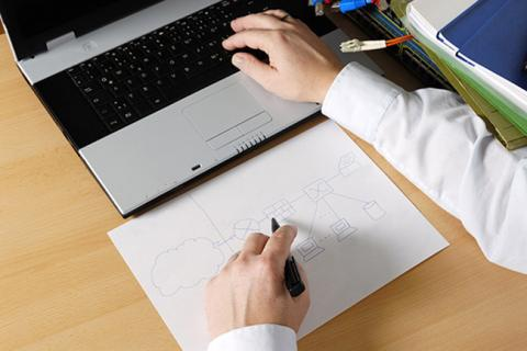 A person at a desk with a laptop and a sketch on paper of system.
