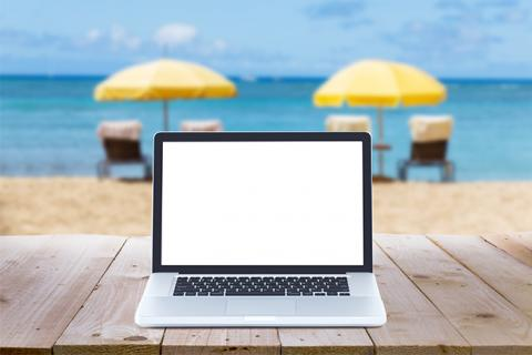 A laptop in front of a view of a beach with two yellow umbrellas