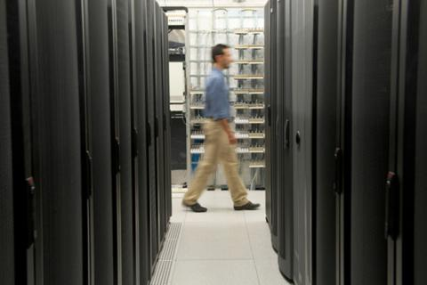 A man walking between two rows of servers.