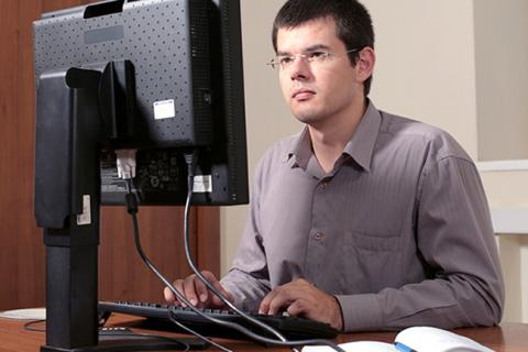 Business Systems Analyst at his computer.